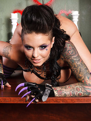 Tattooed buxom bombshell Christy Mack poses naked in the library