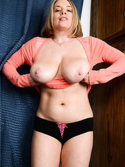 Chubby and sexy MILF Maggie Green doing an eye-catching striptease