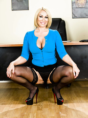 Short-haired blonde milf Mellanie Monroe poses with spread legs on the table