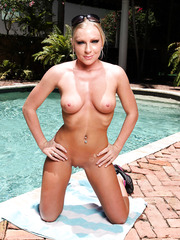 Naked lady Britney Brooks posing outdoors and working with shaved vagina