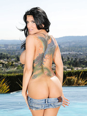 Busty milf Romi Rain poses naked near the pool in sexy sunglasses and high heels