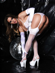 Incredible belle Rachel RoXXX dressed in beautiful white lingerie poses in cryptic black room