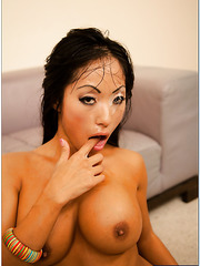 Pretty Asian milf Gaia showing her boobies and sucking a really big dagger